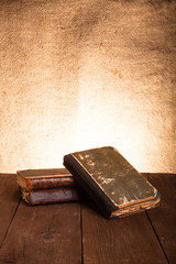 A stack of old books on old wooden table against the background