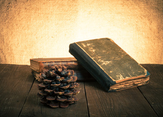 A stack of old books and pine cone on old wooden table against t