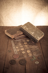Vintage books and coins on old wooden table. Toned