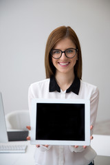 Smiling businesswoman showing tablet computer screen