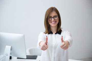Smiling businesswoman standing with thumbs up in office