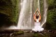 Leinwanddruck Bild - young woman doing yoga in a forest near waterfall
