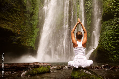 young woman doing yoga in a forest near waterfall - 76489076