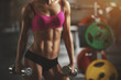 Leinwanddruck Bild - Brutal athletic woman pumping up muscles with dumbbells