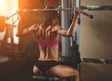 Fototapety Brutal athletic woman pumping up muscles with dumbbells