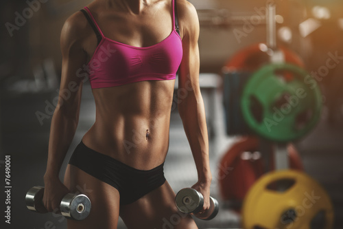 Brutal athletic woman pumping up muscles with dumbbells - 76490001