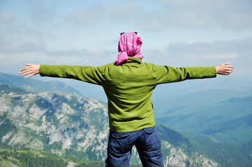 Hiker standing on the top of the mountain with raised hands