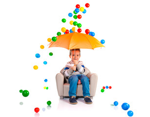 Kid holding an umbrella around colorful balls