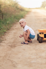 Adorable little blond boy playing with big yellow car - outdoor