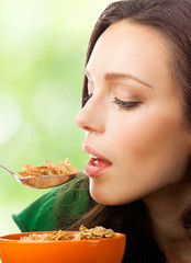 Woman eating muesli or cornflakes