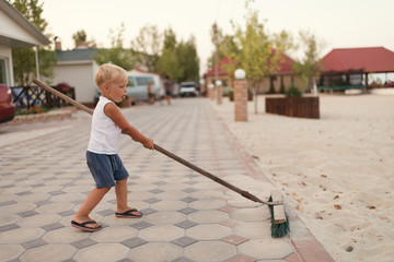 Busy little blond boy cleans the yard with broom.