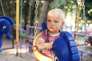 Little blond boy on a swing in a summer park.