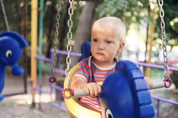 Little blond boy on a swing in a summer park.
