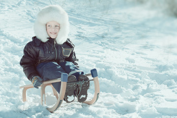 Cute young boy laughing as he is sledging downhill in the snow
