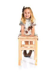 Little blonde girl leaning on chair