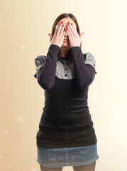 young girl covering her eyes over isolated white background