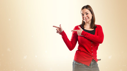 Young pretty woman pointing over white background