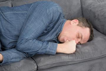 Homme qui suce son pouce sur le canapé