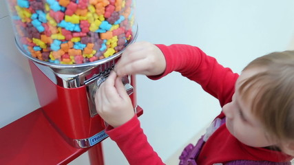 Girl pokes coin in machine sale of sweets in the mall