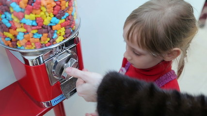 Girl gets candy from machine sale of sweets in the mall