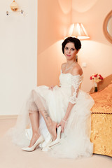 bride is wear on her shoes for the wedding day
