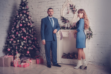 Man and woman in room with Christmas tree and fireplace