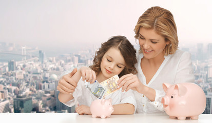 mother and daughter putting money to piggy banks