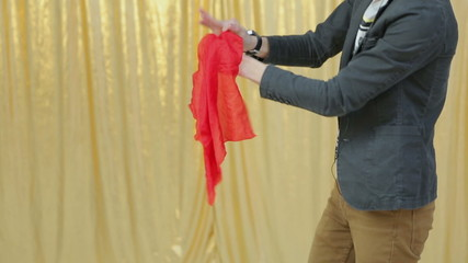 Magician shows tricks with red cloth to a children's representat