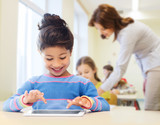little school girl with tablet pc over classroom
