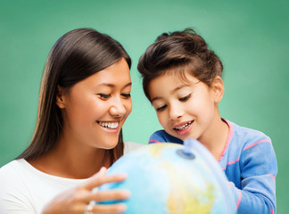 happy teacher and little school girl with globe