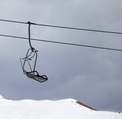 Chair lift and off-piste slope at gray windy day