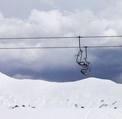 Chair lifts and off piste slope at gray day