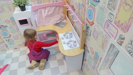 Girl playing with a toy kitchen in the play area of the mall
