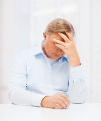stressed old man holding head at home