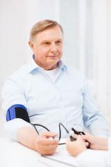 female doctor or nurse measuring blood pressure