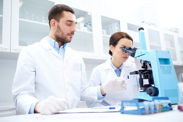 scientists with clipboard and microscope in lab