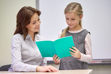 school girl with notebook and teacher in classroom