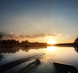 Beautiful dawn morning in an inflatable boat with a paddle