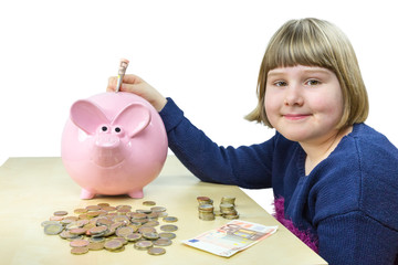 Young girl putting money in pink piggy bank