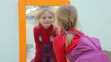 Girl looking at herself in a distorting mirror and smiling