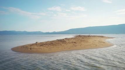 Sandbar on sandy beach surrounded by wavy sea