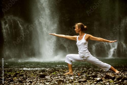 Fototapeta woman meditating doing yoga between waterfalls