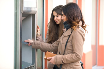 Two young women with credit card in front of the ATM.