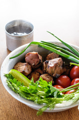 fried meat with greens and vegetables