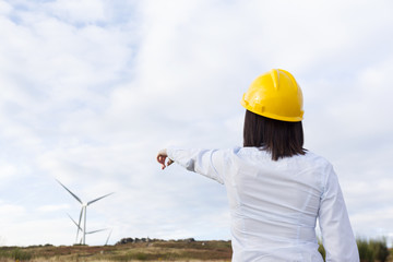 Back view of a female engineer pointing to windmills