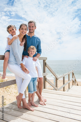 happy family  standing on a wood pontoon in front of the sea - 76513239