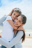 beautiful mom and her daugther at seaside smiling at camera