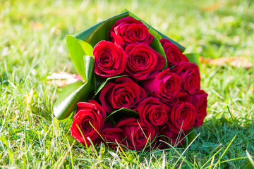 wedding saturate red rose bouquet of bride on grass