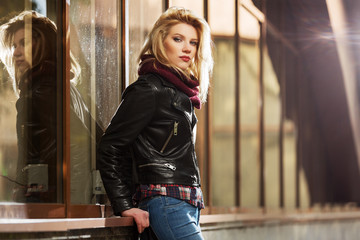 Young fashion blond woman in leather jacket at the mall window