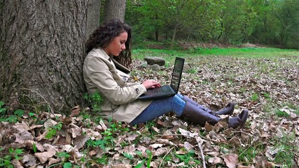 Female student with laptop in the autumn park